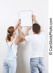 Creating comfort - Young couple hanging up painting on the...