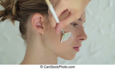 Professional make-up artist making face art in white room