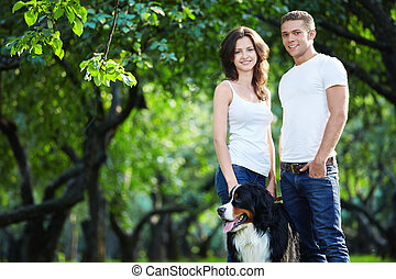 Walking the dog - Young couple walking with a dog in the...