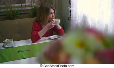 Young woman drinking coffee and smiling at camera happy