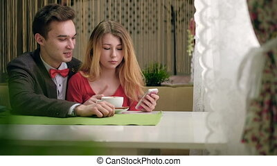 Happy couple taking selfie photo with cellphone sitting in cafe like