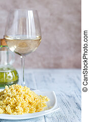 Portion of risotto with glass of white wine