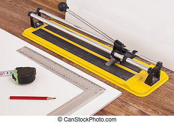 tile cutter on the floor - tile cutter and white tiles on...