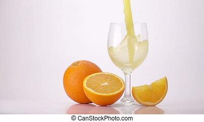 Pouring Orange Juice Into Glass. Light Background. Slow...