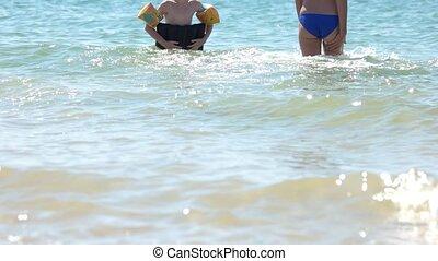 Woman and little girl bathe in the sea. Beach vacation....