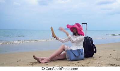 Girl seats on the beach with her bagage and ipad