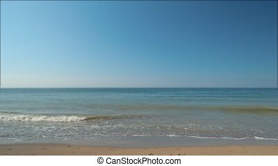 Sand and sea. Blue water with horizon.