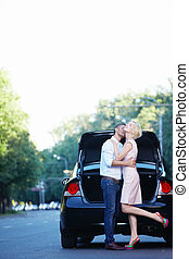 Liking - A young couple kissing on the background of auto