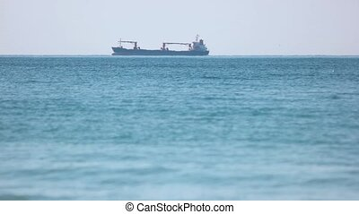 Large barge swiftly sails across the sea. Transportation of...