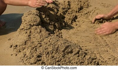 Children play in the sand on the beach. - Children build a...