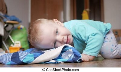 An attractive boy 2 years old is lying on the floor on clothes. He rests after playing at home.