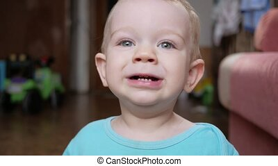 Attractive 2 year old boy looks at the camera and smiles and...