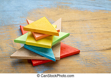 pieces of wooden tangram puzzle - stack of seven colorful...