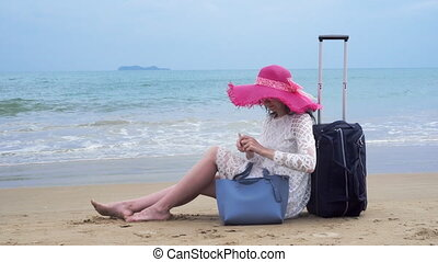 Girl seats on the beach with her baggage and look
