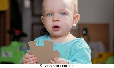 An attractive boy 2 years old picks up a big puzzle. He...