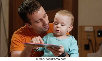 An attractive boy 2 years old and father read a book at home. Dad shows the pictures and the son calls the animals.