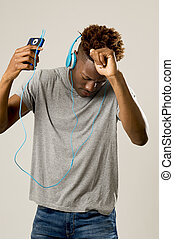 black student man with headphones and mobile phone listening...