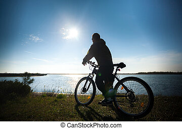 A lone man with bicycle relaxing in sunset sky at sea, river