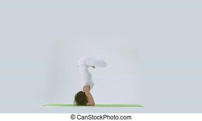 Woman doing yoga handstand on mat in studio - Woman in white...