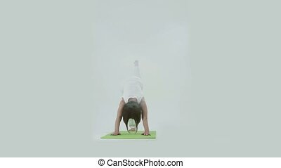 Woman doing yoga on mat in studio - Woman doing yoga on mat...
