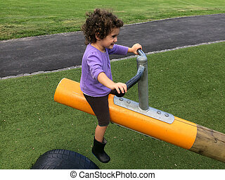 Child girl rides on Seesaw - Child girl (age 03) rides on...