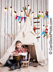 kids playing drum inside wigwam - Kids playing drum sitting...
