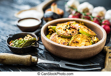 fried zucchini in stoneware with spices - close-up of fried...