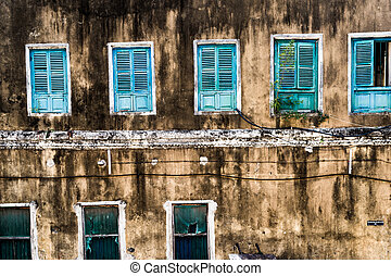 dirty neglected house with colorful windows
