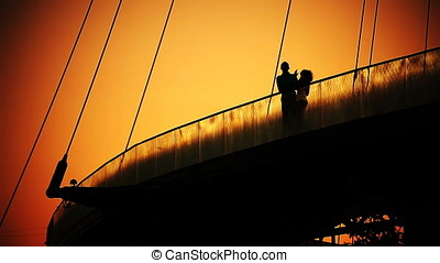Romantic Couple At Dusk On Bridge Back Lit Silhouette.