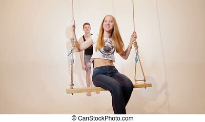 Happy and attractive young couple relax on swing - Young...