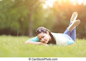 Young pretty woman lying on the grass at summer sunset. Natural happiness, fun harmony.