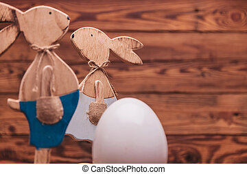 couple of wooden easter bunnies near big egg with copyspace...