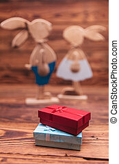 presents boxes in front of wooden easter bunnies couple