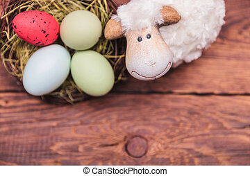 toy sheep near easter eggs basket with copy space bellow -...