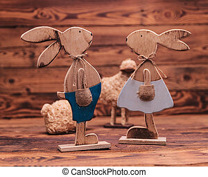 couple of wooden easter bunnies near toy sheep