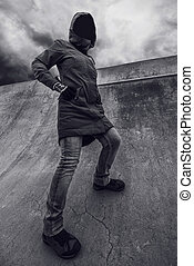 Unrecognizable hooded person in empty skateboarding park -...