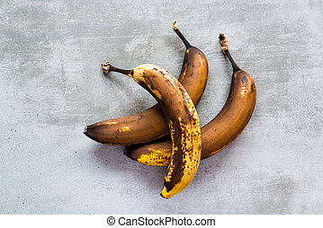 Brown bananas on a concrete table - Three rotten brown...