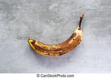 Banana on a concrete table - One rotten brown banana on a...