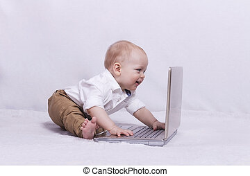 Cute baby boy looking something at laptop - Smiling infant...