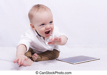Smiling toddler boy playing with a tablet - Cute laughing...