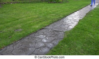 Long stone cobbled path and worker washing it. Garden...