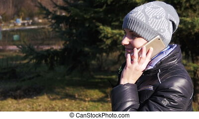 Happy Young Girl Smiling and Talking on a Smartphone in the...
