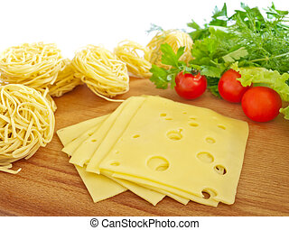 foodstuff - cheese, pasta and vegetables on the hardboard