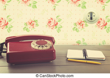 old phone with notebook on the table in vintage room