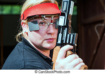 Woman with pistol on sport shooting training