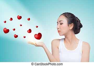beautiful woman celebrating Valentines day blowing red...