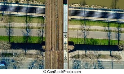 Aerial shot of passenger train moving on railway bridge...