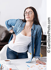 Confused office worker putting her left hand on the table -...