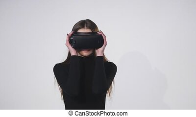 Woman uses a head mounted display. A woman in a virtual reality mask looks around