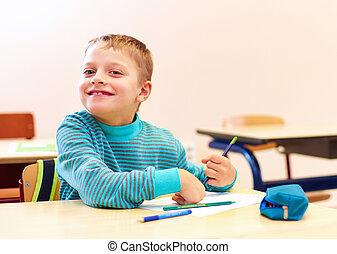 cute boy with special needs writing letters while sitting at...